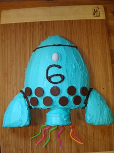 rocket cake made from a football cake pan with icing covered ice cream cone for the candles